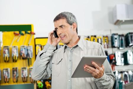 携帯電話を使用している間デジタル タブレットを保持している男