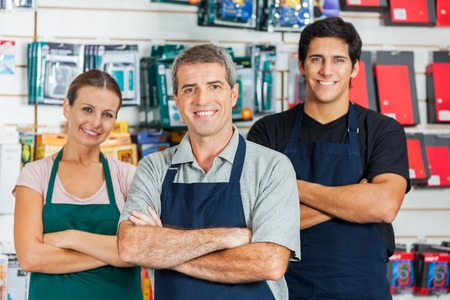shopkeeper: Salespeople Standing Arms Crossed In Hardware Shop