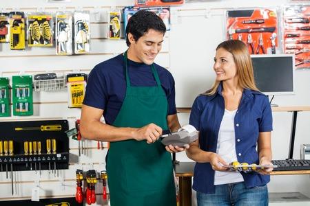 Woman Looking At Worker Swiping Credit Card photo