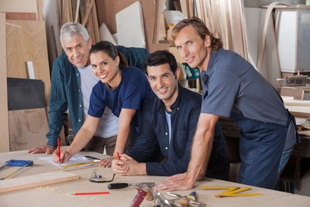Confident Carpenters Working At Table In Workshop photo
