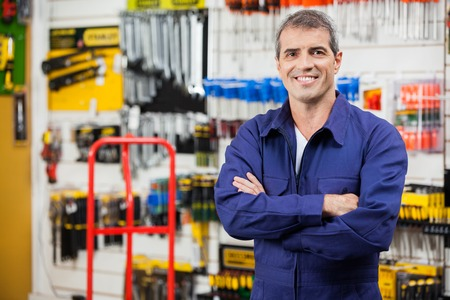 Worker With Arms Crossed In Hardware Shop