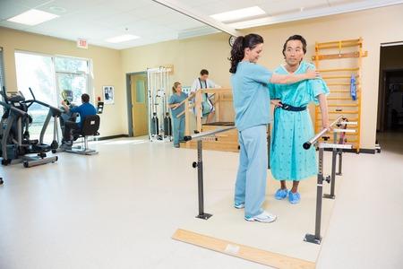 f�sico: Los terapeutas ayudar a los pacientes en el hospital Gimnasio Foto de archivo