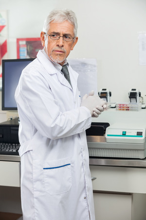 Scientist Standing By Analyzer In Lab