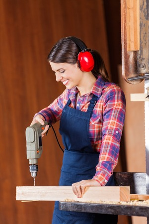 Female Carpenter Drilling Wood In Bandsaw photo
