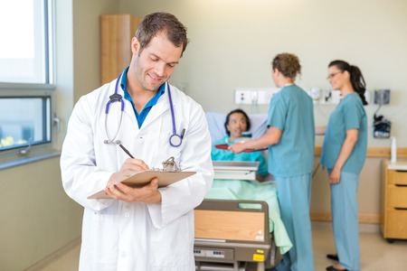 Doctor Writing On Clipboard With Nurses And Patient In Hospital