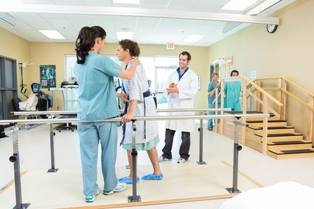 therapy room: Physical Therapist Assisting Patient In Walking Stock Photo
