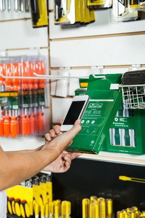 retail display: Hands Scanning Products Barcode Through Cellphone Stock Photo