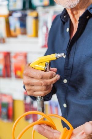 compresor: Hombre que sostiene el compresor de aire Manguera En Departamento