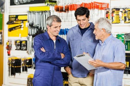Ältere männliche Arbeiter Blick auf Kunden mit Klemmbrett in der Hardware-Shop