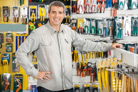 ハードウェアの店で立って幸せな男