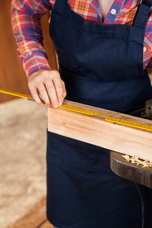 Midsection Of Carpenter Measuring Wood photo