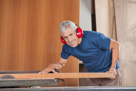 woodworker: Portrait of happy senior carpenter cutting wood with tablesaw in workshop