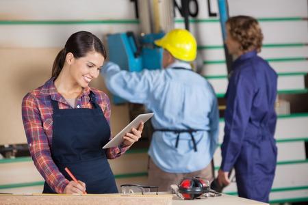 Female Carpenter Using Digital Tablet In Workshop photo