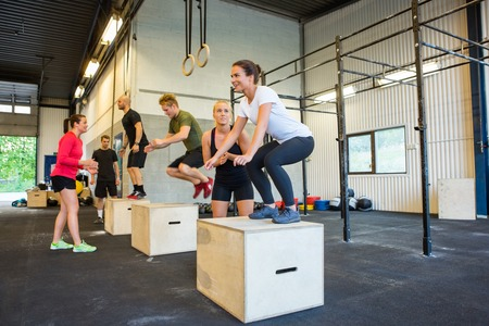 cross: Athletes Doing Box Jumps At Gym Stock Photo