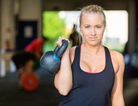 mujer deportista: Confiado Atleta Femenina de elevación Kettlebell Foto de archivo