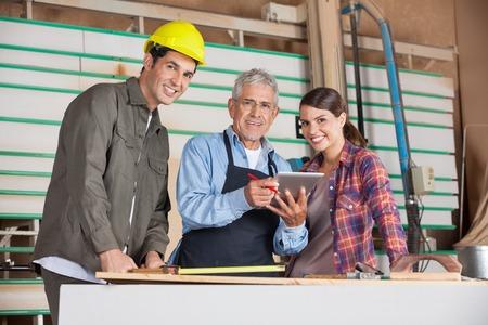 young engineer: Carpenters Using Digital Tablet In Workshop