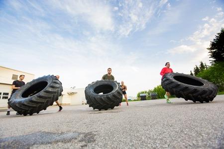 Atleti Fare Tire-Flip Exercise Archivio Fotografico