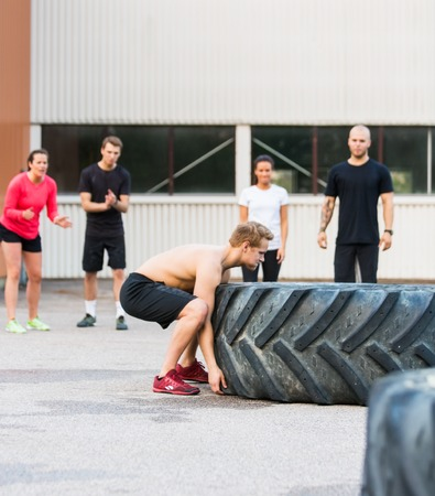 flipping: Athletes Motivating Friend In Flipping Tire Stock Photo