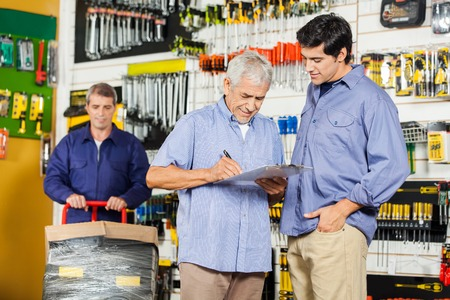 hardware: Customers Writing On Checklist In Hardware Store