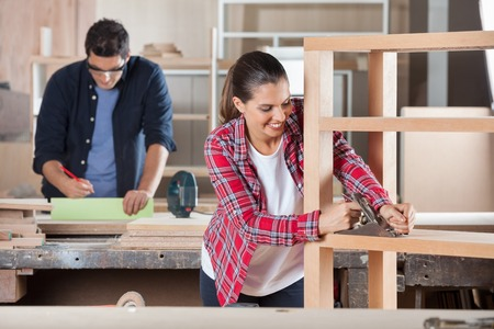 planer: Carpenter Shaving Wood With Planer In Workshop Stock Photo