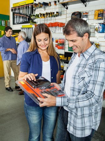 Happy Couple Buying Tool Set In Hardware Store photo