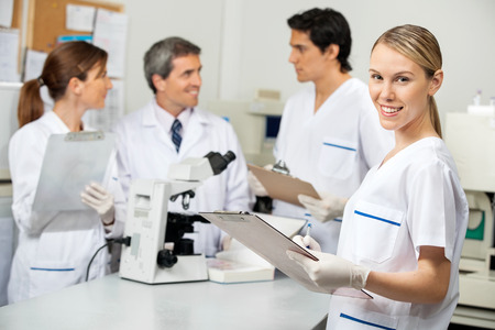 med: Female Scientist Writing On Clipboard In Laboratory
