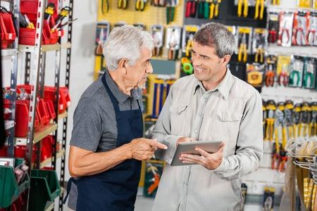 hardware: Vendedor con el cliente que usa la tablilla digital en tienda