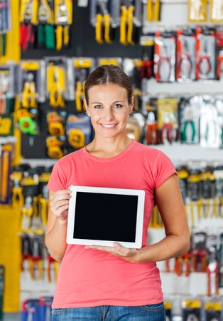 Woman Displaying Digital Tablet In Hardware Shop photo