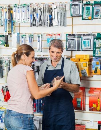 Salesman Guiding Customer In Hardware Store photo