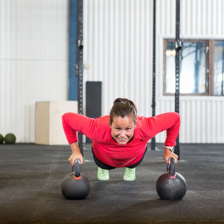 pushup: Woman Doing Pushup Exercise With Kettlebell Stock Photo