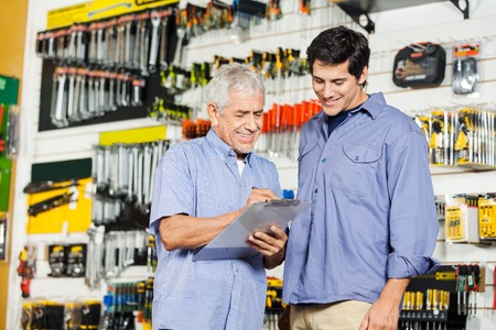 hardware: Customers Checking Checklist In Hardware Store