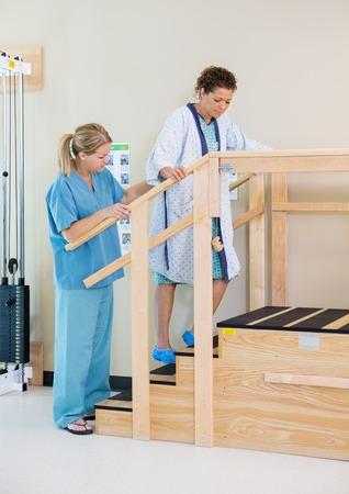 Terapeuta Assistere il paziente femminile in movimento Al piano superiore Archivio Fotografico
