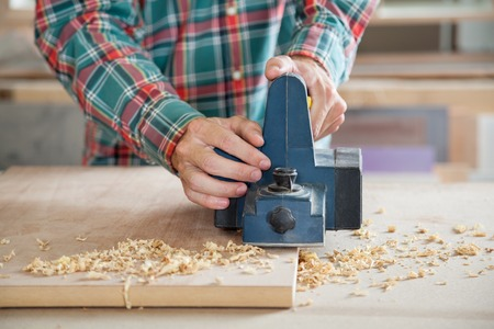 woodworker: Carpenter Working With Electric Planer On Wood
