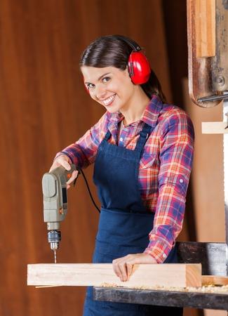 Female Carpenter Using Drill Machine On Wood photo