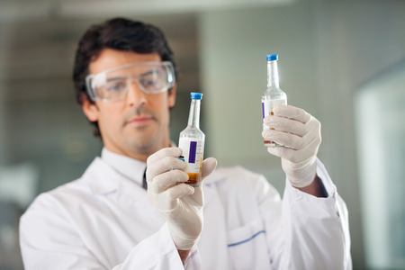 research facilities: Scientist Examining Urine Samples In Lab