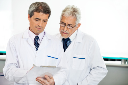 research facilities: Technicians Discussing Over Clipboard