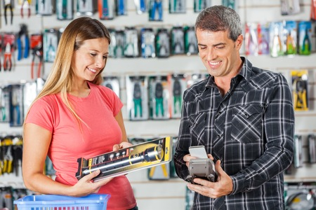 flashlight: Couple Paying For Flashlight Through Smartphone In Store Stock Photo