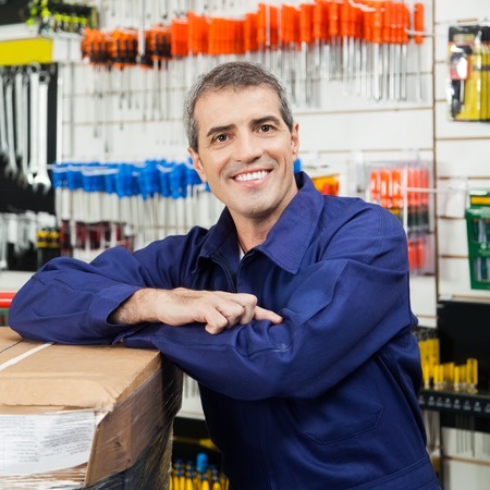 retailer: Worker Leaning On Tool Package In Hardware Shop