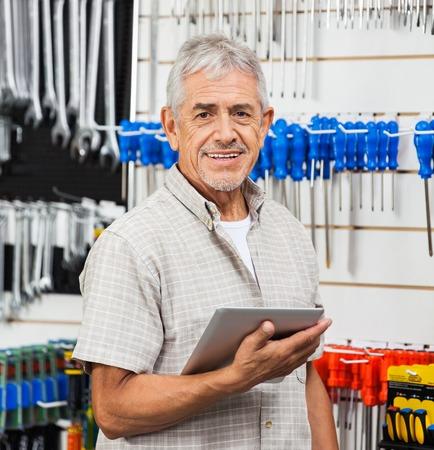 Senior Customer Holding Tablet Computer In Hardware Store Stock Photo
