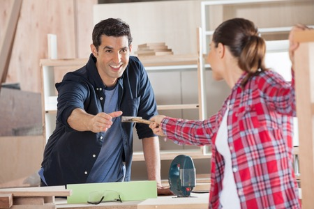 woodworker: Carpenter Receiving Hammer From Female Colleague