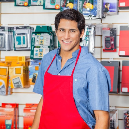 Handsome Salesman In Red Apron Smiling At Hardware Shop Stockfoto