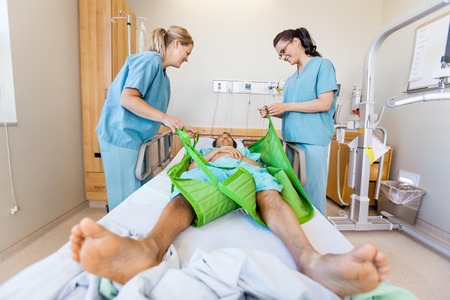 transferring: Nurses Preparing Male Patient Before Transferring Him On Sling L