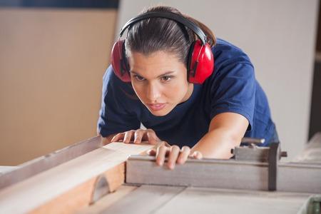 Weibliche Carpenter Schneiden von Holz mit tablesaw Standard-Bild