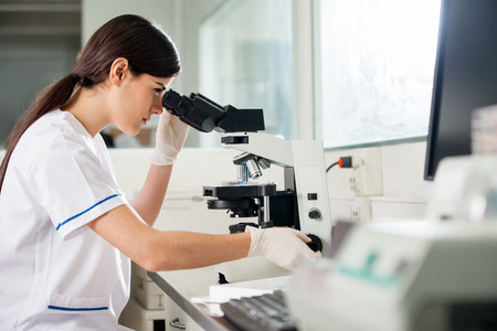 scientists: Científico de sexo femenino que mira a través del microscopio Foto de archivo