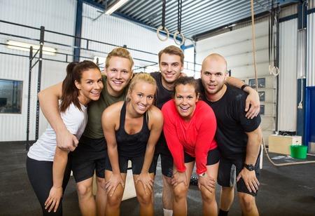 Gruppo di atleti felice permanente alla scatola di fitness croce Archivio Fotografico