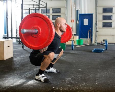 アスリート: オスの運動選手ジムでバーベルを持ち上げる