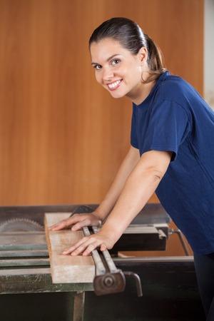 Female Carpenter Using Tablesaw In Workshop photo