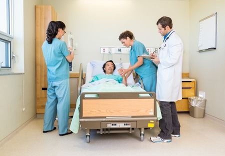 hospital patient: Nurses And Doctor Examining Patient In Hospital