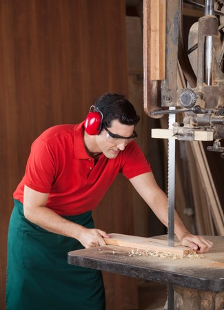 woodworker: Carpenter Cutting Wood With Bandsaw