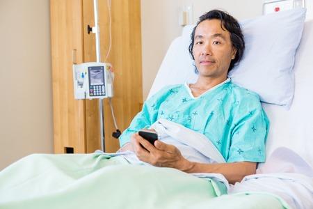 persona enferma: Holding Paciente del tel�fono m�vil mientras descansa en la cama de hospital Foto de archivo